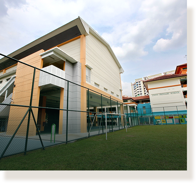 Unity Primary School has an indoor sports hall elevated over a court.