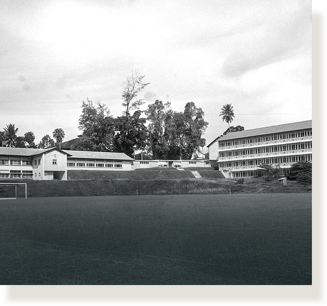 A four-storey school building with a playing field (1958).